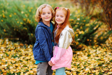 two children - a small boy with blond curly hair and a girl with red hair hugging holding hands against the background of autumn yellow leaves and Park. The concept of autumn, love, friendship.