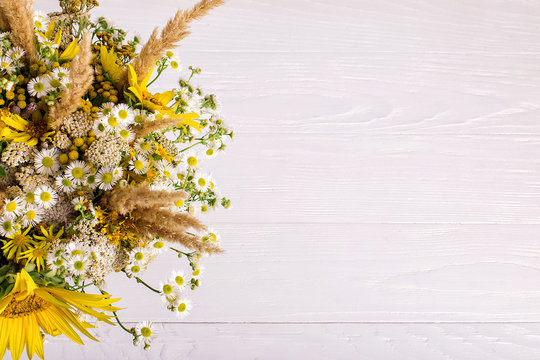 Wildflowers in a handmade vase, on a white background on the table. Copy space.
