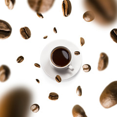 Cup of coffee and coffee beans in flight on white background