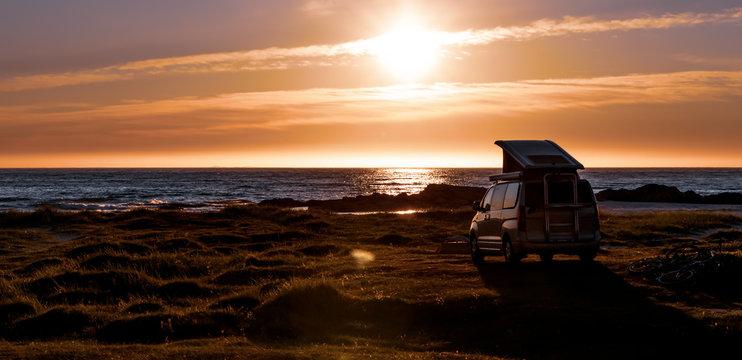 Camping car minivan on the beach at sunset Lofoten beach.