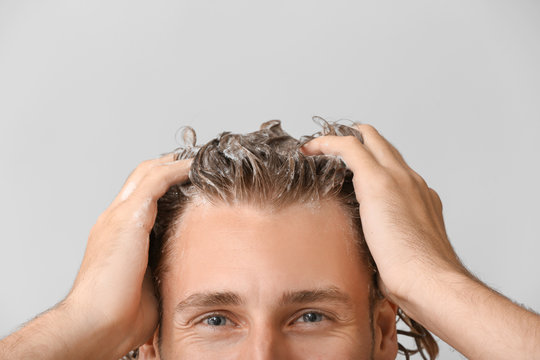 Handsome young man washing hair against grey background