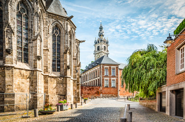 Fotomurales - Cobbled street with church and belfry tower in Walloon city center of Mons, Hainaut, Belgium.