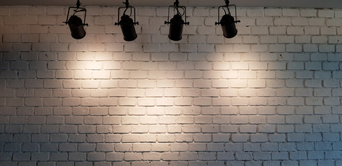 Hanging spotlight illuminate at white brick wall background with copy space