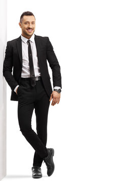 Young cheerful man in a black suit leaning on a wall