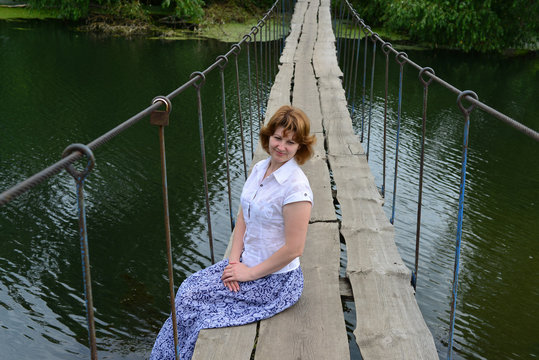 Woman sitting on a wooden bridge over the river