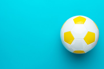 Top view photo of white and yellow soccer ball as football concept . Minimalist flat lay image of leather football ball over blue turquoise background with copy space and right side composition.