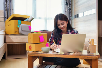 Asian business woman writes note on daily about order from customer product, Working at home office with eCommerce system. Small and Medium Enterprises Concept. Fototapete