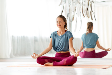 mindfulness, spirituality and healthy lifestyle concept - woman meditating in lotus pose at yoga studio Wall mural