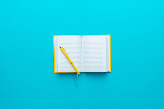 Top view of opened notebook and yellow pen over it in the centre of turquoise blue background with copy space. Minimalist flat lay image of blank diary and ball-point pen