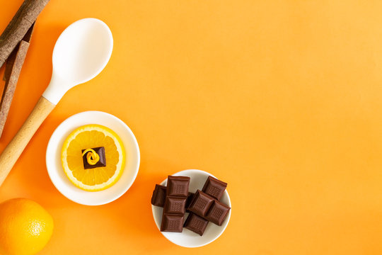 Chocolate pieces over orange slice, full orange, cinnamon sticks and white cooking spoon over orange background with copy space.