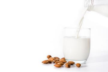 Fototapeta Pouring almond milk in glass isolated on white background. Copyspace obraz