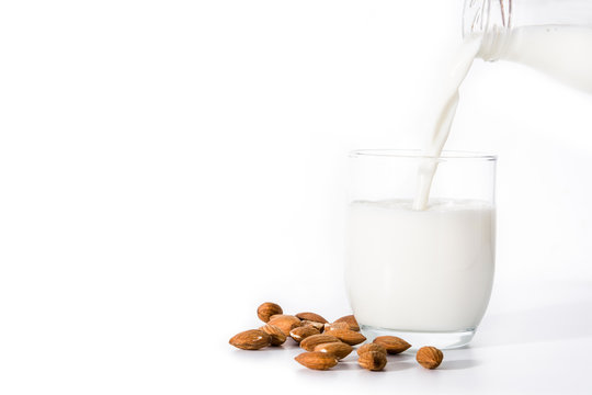 Pouring almond milk in glass isolated on white background. Copyspace