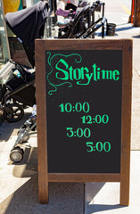 Children's STORYTIME blackboard sign with strollers on urban street.