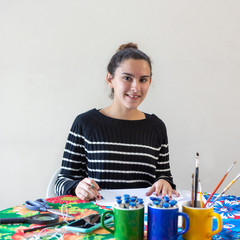 Young talented woman artist sitting at the table with flowered tablecloth making art with pencils, paper, scissors, magnifying glass, brush and paints in colorful mugs while listening to music on cell