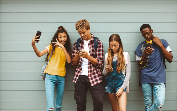 Teenage friends looking at their mobile phones