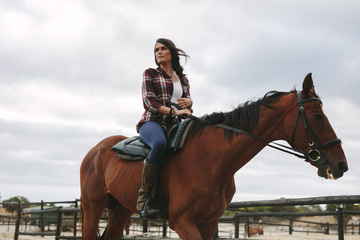 Woman riding her horse in corral