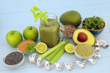 Health food diet drink with fresh fruit, vegetables, matcha powder, flax, chia and hemp  seed on blue wood background with tape measure. High in omega 3, antioxidants, vitamins and dietary fibre.