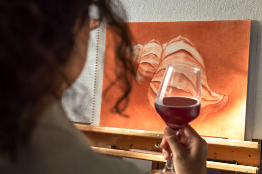 Woman drinking a glass of wine to celebrate that she has finished her painting. Artist contemplating his finished work.