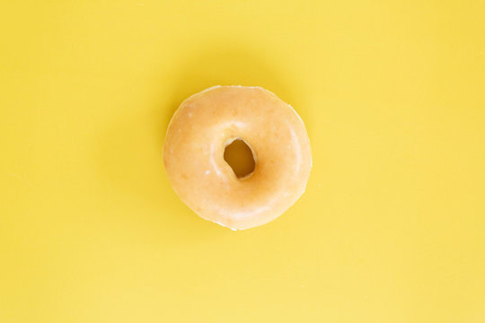 Plain Glazed Donut on Bright Yellow Background, Copy and Text Space
