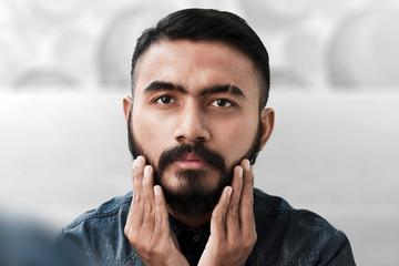 Handsome bearded man touching his beard