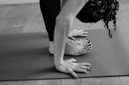 Woman practicing yoga full forward bend touching the mat.