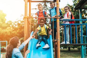 School children playing on the slide.