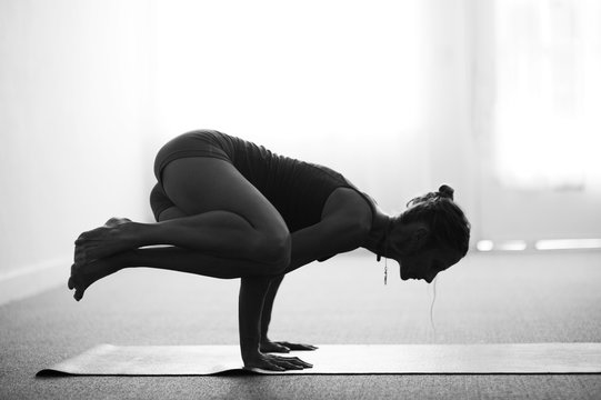 Classical black and white art photography of a woman practicing advanced yoga pose indoors on a yoga mat
