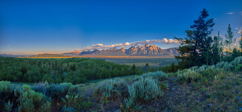 Panoramic view of early sun rays on the Grand Teton mountain range.