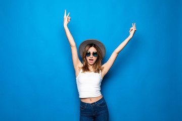 Cheerful healthy girl raising her hands up with enjoyment isolated on blue background