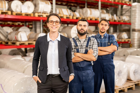 Happy young elegant female leader of engineering team and two men in workwear