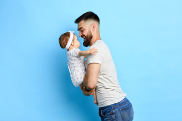 positive caring dad enjoying time with baby. close up side view photo. isolated blue background. I love you, my daughter. You are my life