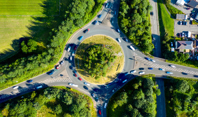 Composite aerial image of traffic using a small roundabout with multiple connecting roads