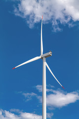 A wind turbine and blue sky with clouds. Large three-bladed horizontal-axis wind turbines produce the overwhelming majority of windpower in the world today.