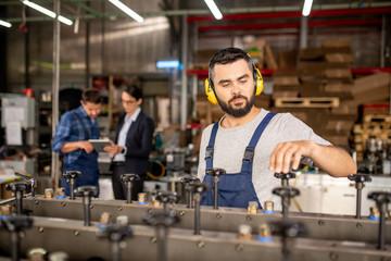 Young bearded mechanic in protective headphones repairing industrial machine
