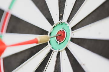 Close-up image with a dart in the bullseye of a practice target