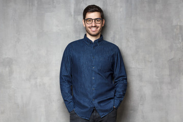 Young smiling entrepreneur wering eyeglasses and denim shirt, standing against gray textured wall...