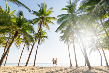 Papiers peints Palmier Couple standing on sandy beach among palm trees on sunny morning