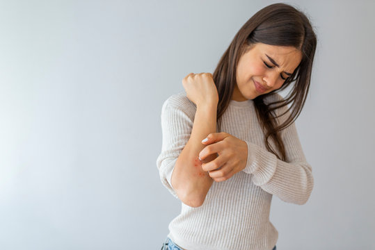 Women scratch the itch with hand , Concept with Healthcare And Medicine. Woman scratching arm on grey background. Allergy symptoms. Woman scratching her arm.