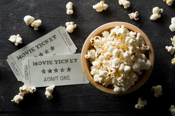 Movie tickets and bowl of popcorn on dark background. Home theatre movie or series night concept. Flat lay top view from above