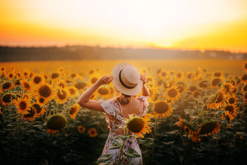 bright delightful atmospheric photo, summer field of sunflowers, large yellow flowers and girl in light beige dress and straw boater, lady against hot sun, model from back, no face, free country life Wall mural