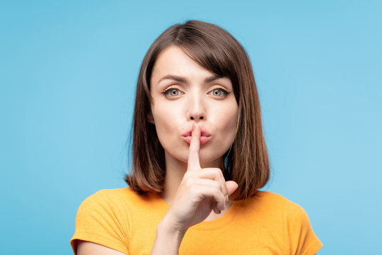 Young female keeping forefinger by her pouted lips while asking to be quiet
