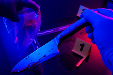 Forensic science, murder weapon and criminal investigation concept with detective wearing latex gloves bags kitchen knife to send to lab in dark crime scene illuminated by red and blue cop car lights - fototapety na wymiar