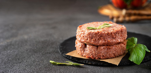 Two raw vegan patties on dark grey background Fotoväggar