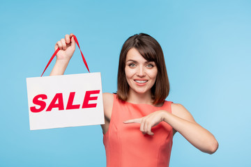 Happy young brunette woman in red dress pointing at sale announcement