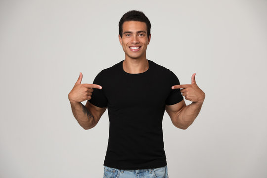 Handsome young African-American man in blank t-shirt on light background. Space for design