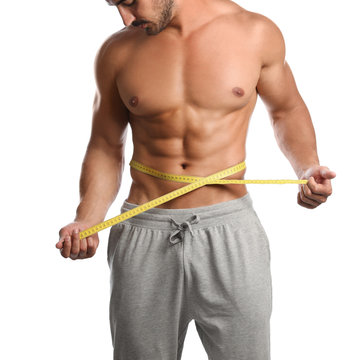 Young man with slim body using measuring tape on white background, closeup view