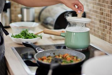 Dedicated Caucasian woman opening boiling pot. Vegetarian dinner preparation concept.