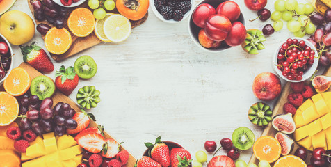Wall Mural - Healthy raw breakfast background, cut fruits, strawberries raspberries oranges plums apples kiwis grapes blueberries mango persimmon, on white table, copy space, top view, toned, banner