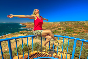 Coral coast, Indian Ocean, Australia. Carefree woman at Eagle Gorge Lookout platform in Kalbarri National Park, Western Australia. Caucasian girl enjoys in popular travel destination. Blue sky.