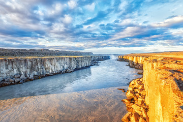 Beautiful Icelandic Landscape: Picturesque morning scene of Jokulsa a Fjollum river with amazign creme color water, Selfoss waterfall in background. Travel background for Iceland. Basalt lava nature.